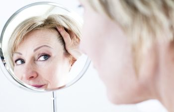 Mature woman looking at her face in a mirror and considering facial Anti-Aging Treatments in Beverly Hills CA