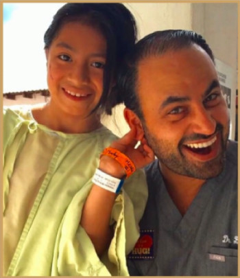 Dr. Ben Talei smiling with his young patient