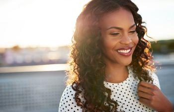 A happy Afro-American woman with beautifully shaped nose after Rhinoplasty in Beverly Hills, CA.